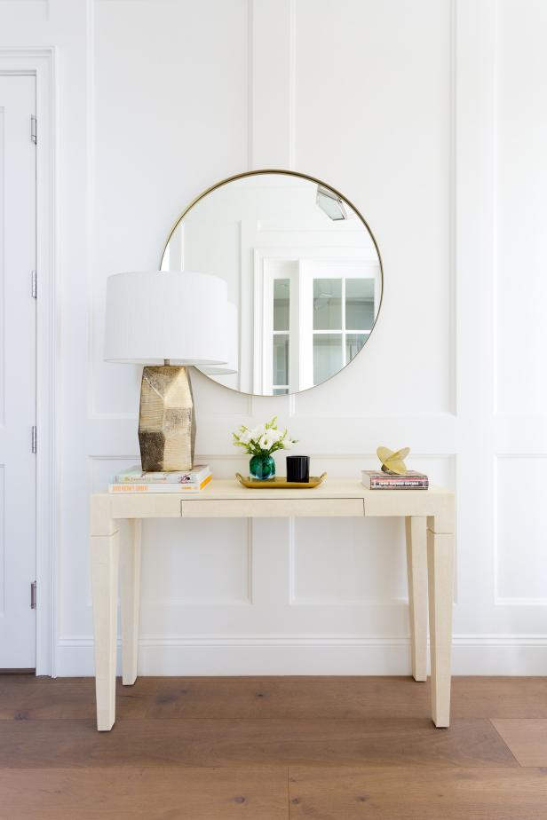 transitional white foyer with round mirror