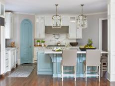 White Open Plan Kitchen With Blue Arched Door