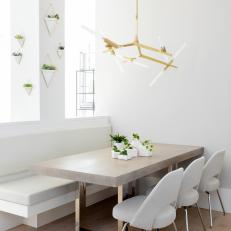 Modern White Dining Room With Built In Banquette And Brass And Glass Chandelier