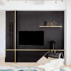Modern Living Room Detail With Black Accent Wall And Floating Shelves And Task Lighting
