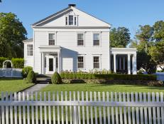Traditional White Country Colonial With Landscaping And White Picket Fence