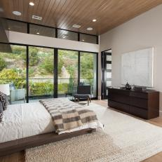 Modern Neutral Bedroom With Oversized Windows And Wood Ceiling