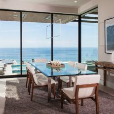Modern Dining Room With Glass And Metal Dining Table And White Upholstered Chairs