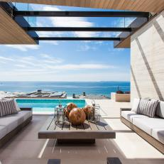 Modern Covered Patio Living Room With Upholstered Seating And Views of the Pool