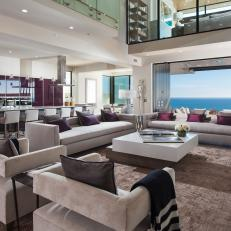 Open Concept Living Room And Kitchen With Modern Upholstered Furnishings And Purple Accents