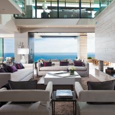Modern Living Room With Gray Upholstered Seating And Gas Fireplace With Tile And Ocean Views