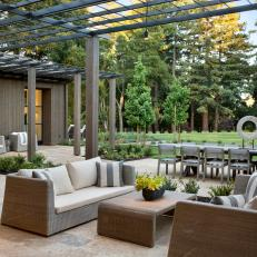 Modern Outdoor Dining And Sitting Area With Metal Pergola And Contemporary Wicker Sofas