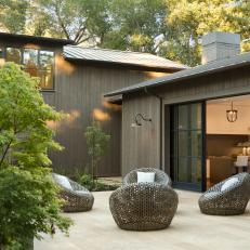 Modern Farmhouse With Retractable Window Wall And Outdoor Sitting Area With Contemporary Woven Chairs