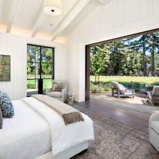 Modern White Farmhouse Bedroom With Retractable Window Wall And Exposed Beams And Rafters