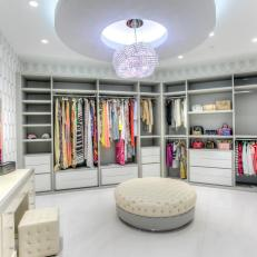 Boutique-Style Closet With Sparkling Chandelier, Tufted Ottoman