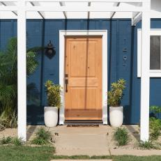 Contemporary Blue Home Exterior With Neutral Wood Front Door