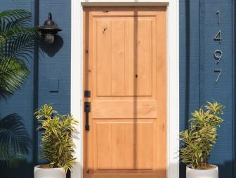 Tropical Blue Home Exterior with Neutral Wood Door