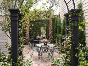 Brick Courtyard With Wrought Iron Dining Set And Mirror