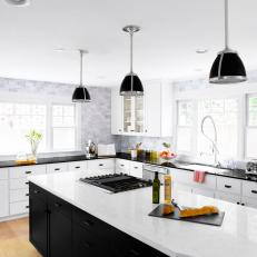 Black and White Chef Kitchen With Marble Backsplash