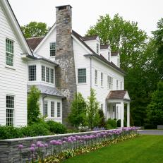 White Colonial Home with Large Stone Chimney