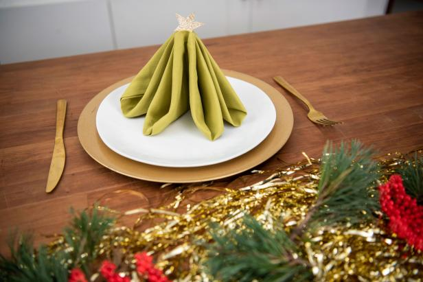 Impress your guests this holiday season with a Christmas tree-shaped napkin at the table.