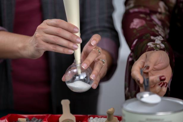 Use a funnel with a narrow opening to fill one-third of a clear ornament with hot cocoa mix.