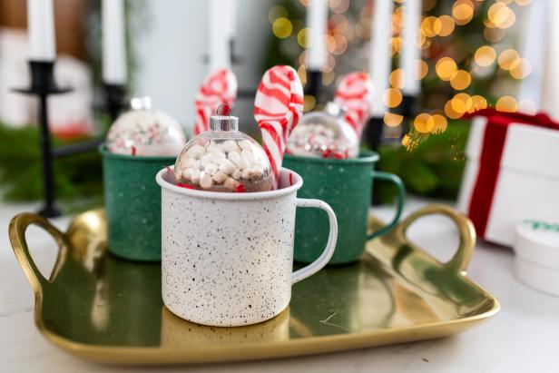 Gold tray with hot cocoa ornaments and peppermint spoons in mugs.