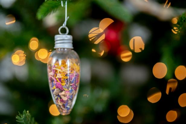 Clear ornament filled with flower seeds and dried flowers.