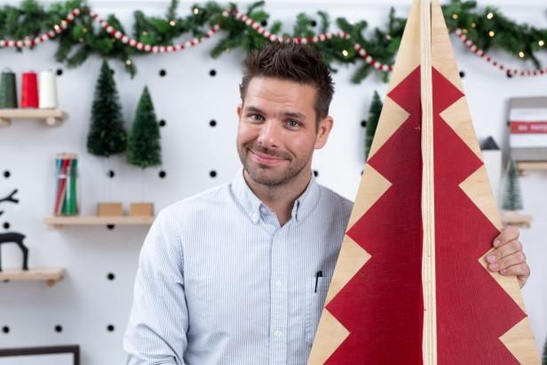 Man Standing With Painted Wooden Christmas Tree