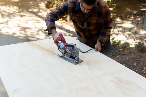 Using a saw, cut the plywood at the marked lines.