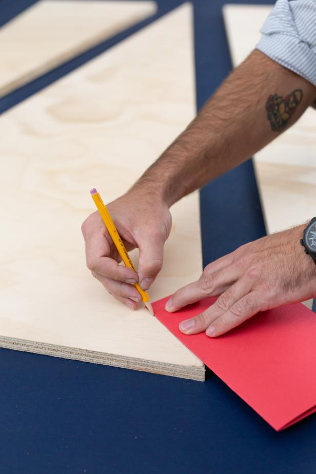 Using a pencil and a piece of folded paper, mark the edges for the Christmas tree on the plywood.