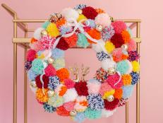 Celebrate the ho-ho-holidays with this festive pom-pom wreath that's as merry and bright as Rudolph's nose.