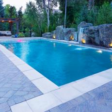 Swimming Pool With Waterfall And Landscape Lighting