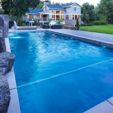Grand Backyard With Swimming Pool And Large Rock Water Feature