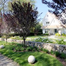 Tudor Home Exterior With Stone Retaining Wall