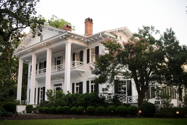 Large White Home With Four Columns and Black Shutter Windows