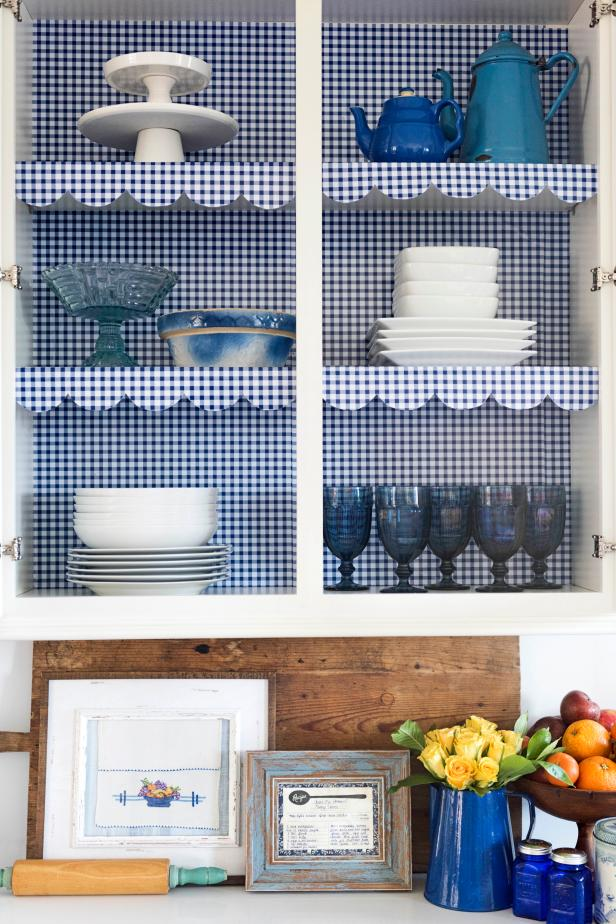 Give your kitchen a big boost of cozy cottage style by inexpensively lining the shelves with gingham shelf paper and framing family recipes and a hand-me-down tea towel as art.