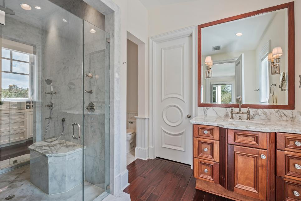 Master bath with wood and marble vanity and glass shower.