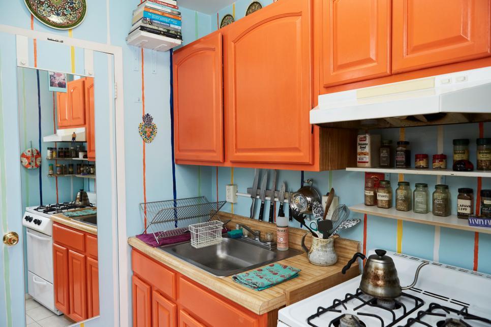 Bright Orange Kitchen Cabinets Sit Against A Blue Striped Wall Hgtv