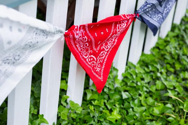 A Patriotic Pennant Banner Made of Bandanas On a Fence