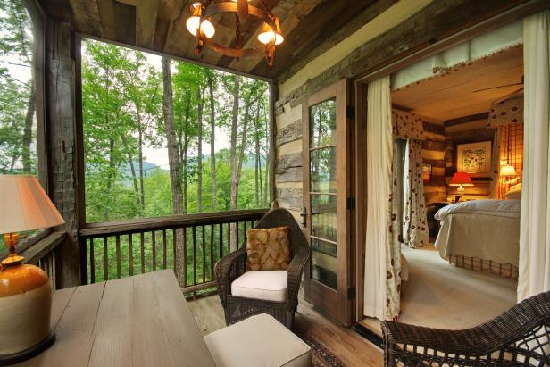 Private Deck With Wicker Chairs Looking Into Log Cabin Bedroom