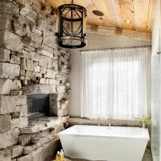 Rustic Bathroom With Soaking Tub And Stone Fireplace