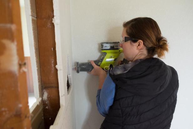 Woman removing a wall during an interior remodel.
