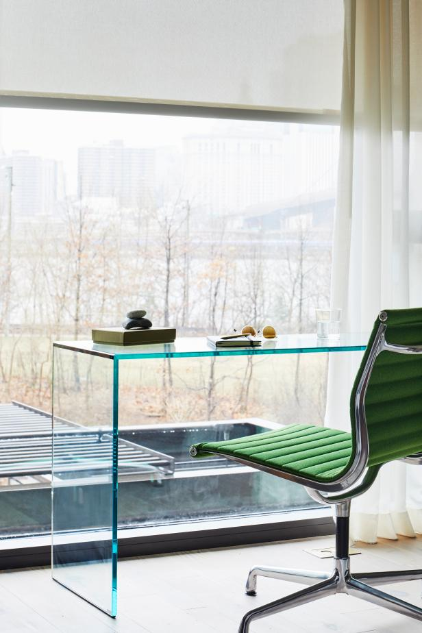 Large Glass Desk Situated In Front Of Floor-To-Ceiling Window