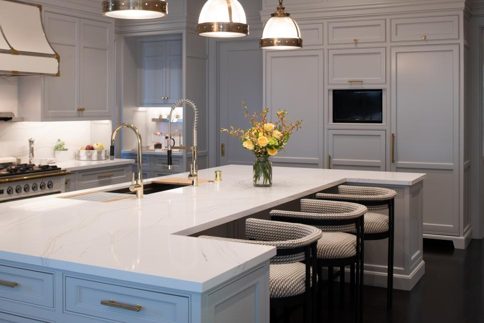 Kitchen With White Cabinets, Large Island and Industrial Pendants