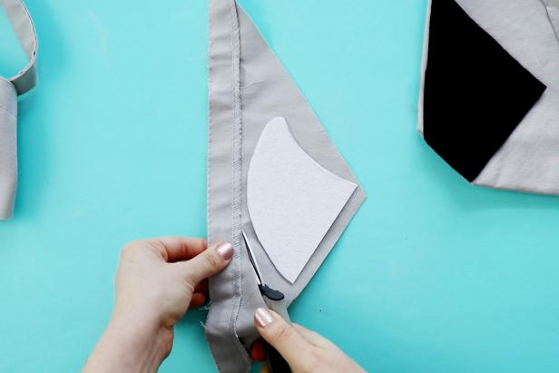 Use the extra fabric you cut from the tote bag to cover the stiff felt for the shark bag's fin.