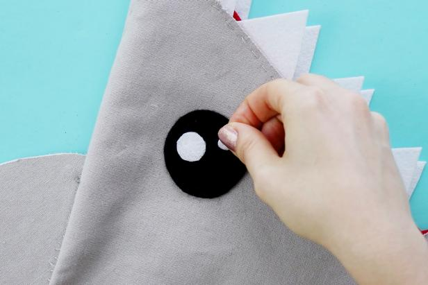 Cut two pieces of felt and attach to tote with glue or sew on.