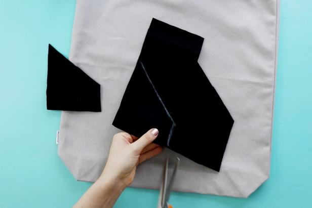 Cut out black felt. You'll attach this to the bottom of the gray tote bag to create the illusion of a shark's tail.