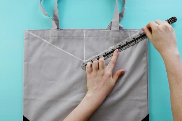 With help from a ruler, trace a triangle on the mouth of the tote bag.