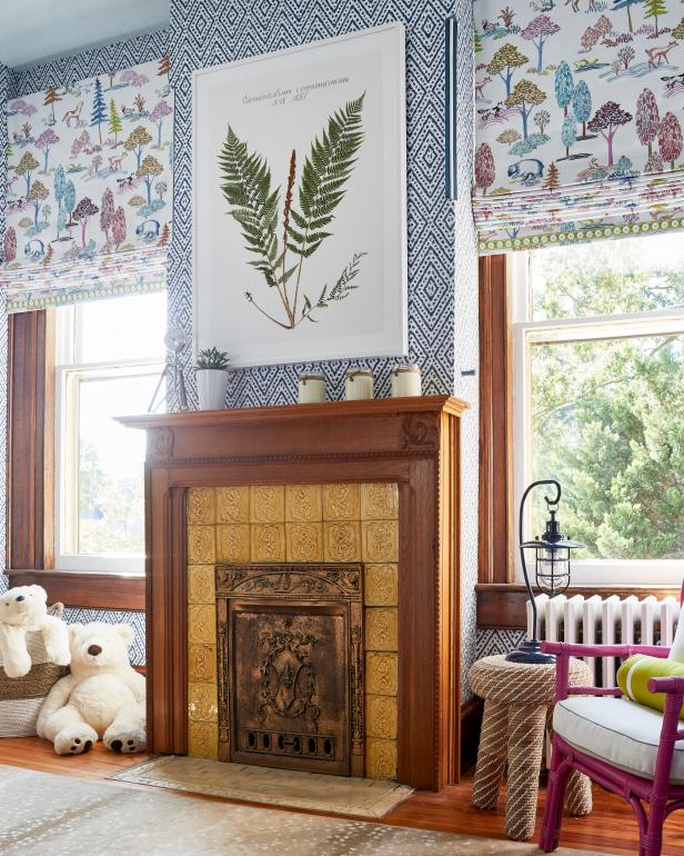 Patterned Roman Shades Flank Warm Wood-Trimmed Fireplace