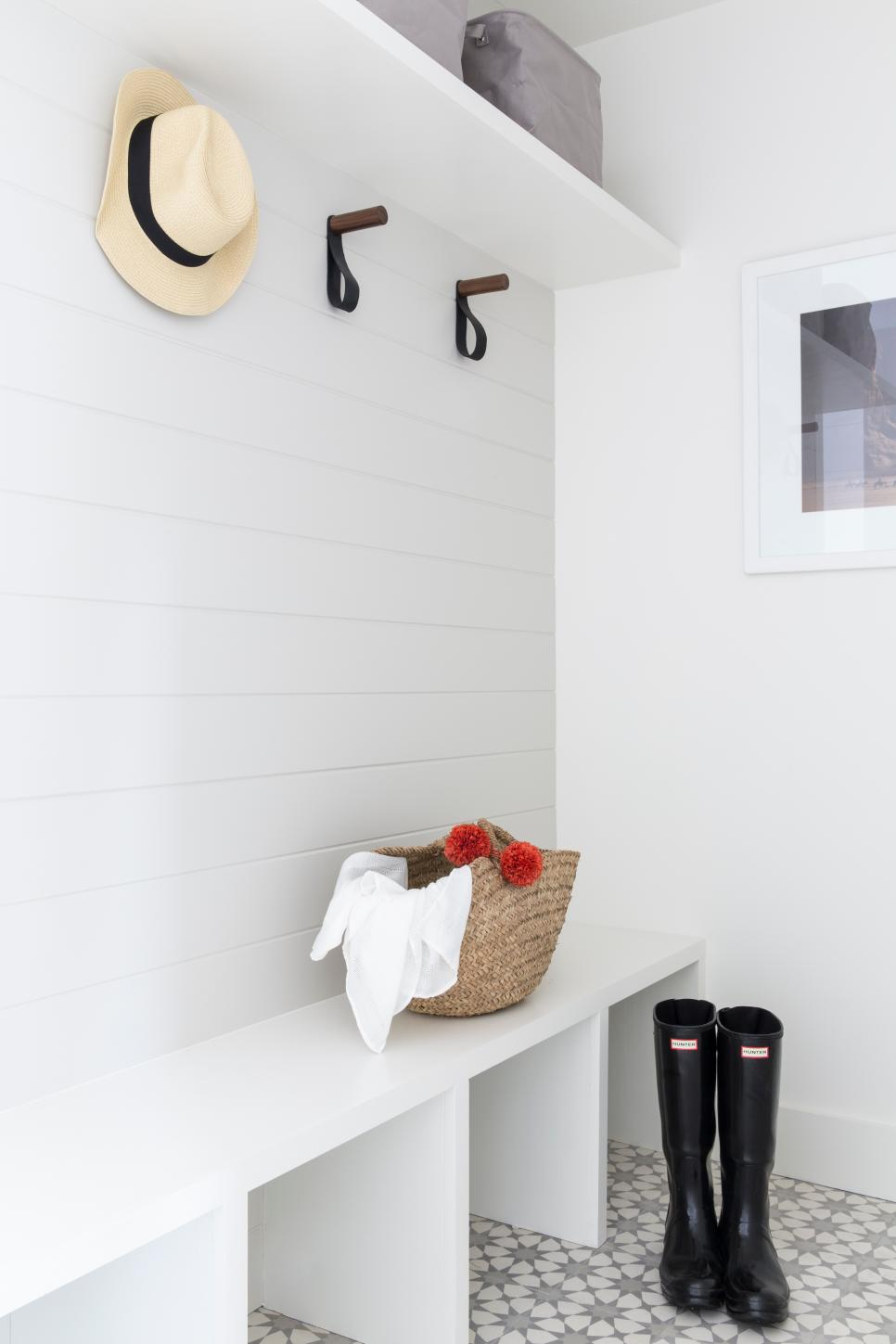 Modern Foyer With White Tiles, Hat On A Hook, And Boots On Tile Floors