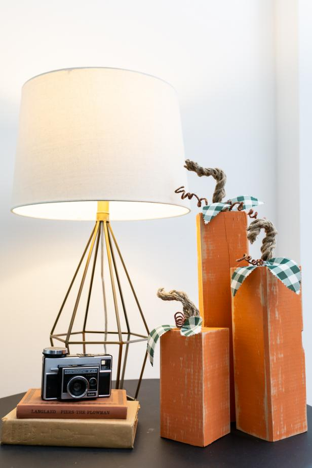 Three Wooden Pumpkins Sitting on a Side Table Beside Lamp