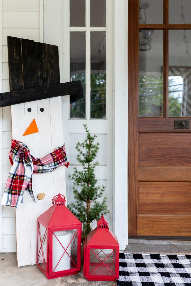 This snowman decoration is made out of wood and painted and decorated to look like a real snowman. The scarf and carrot nose really sell the look.