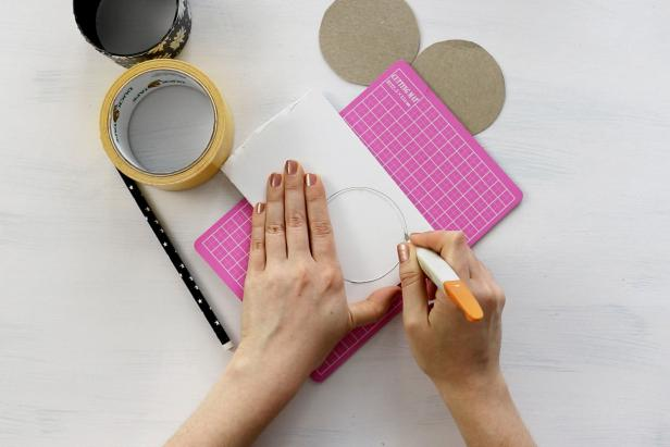 Trace the outside of the duct tape roll onto cardboard twice and trace the inside of the roll onto foam board once. Cut the cardboard circles out with scissors and then use a craft knife to cut out the foam circle.