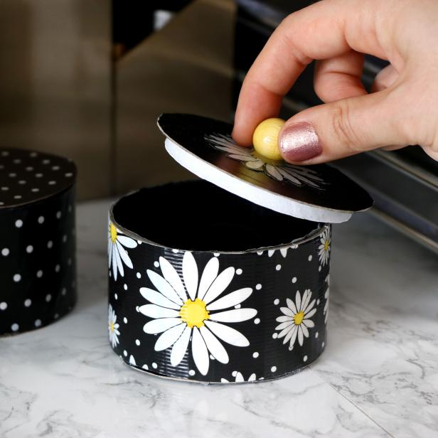 Use your DIY skills to craft a handy storage box out of an empty duct tape roll and decorative tape.